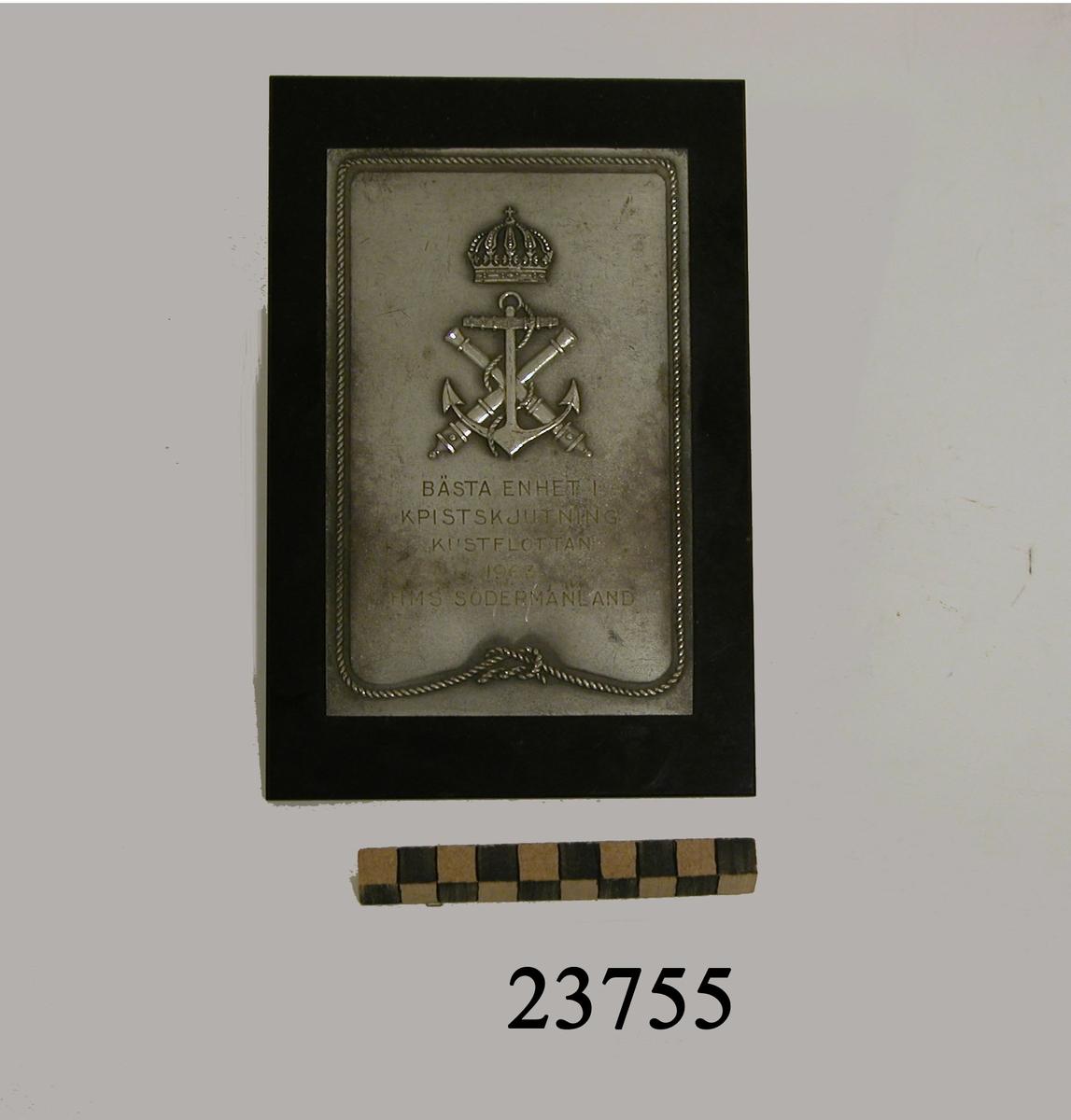 Rektangulär plakett av vit metall fäst på platta av bakelit. Längs sköldens kant en tross i relief. I övre delen på plaketten två korslagda eldrör och stockankare, krönt av kunglig krona. Där under ingraverad text : BÄSTA ENHET I KPISTSKJUTNING KUSTFLOTTAN 1963 H M S SÖDERMANLAND.