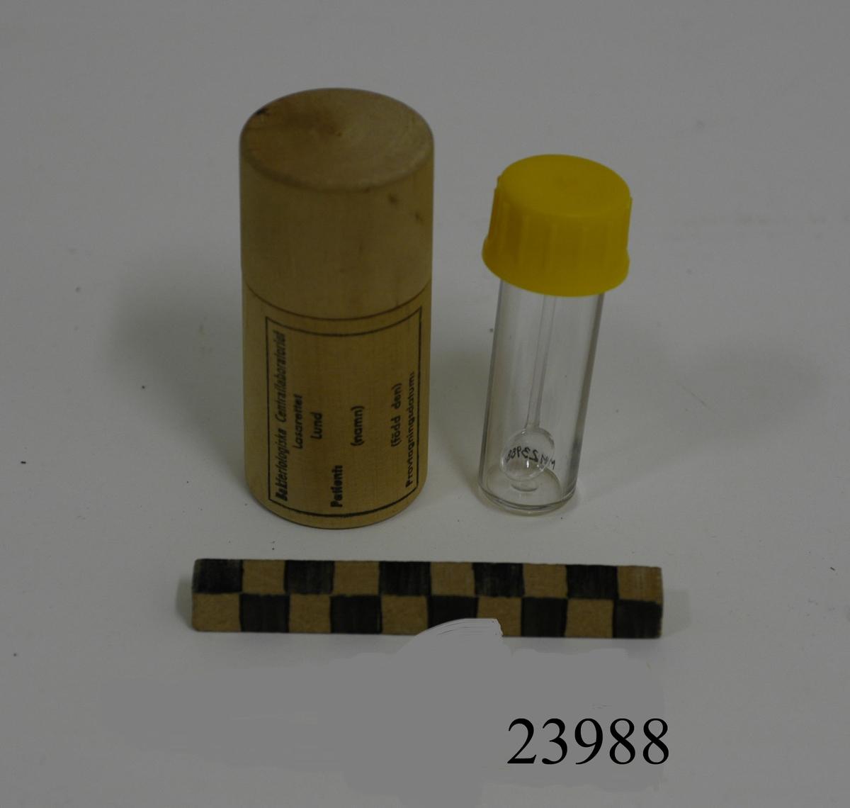 Provtagnings burk bestående av: förvaringsburk av trä, cylindrisk med skruvlock. På utsidan stämplad etikett med text: Bakteriologiska centrallaboratoriet Lasarettet Lund. Patient: (namn), (född den). Provtagningsdatum: I förvaringsburken, provtagningsburk av plast med gul skruvkork. På insidan av locket en fastsatt 60 mm lång sked.