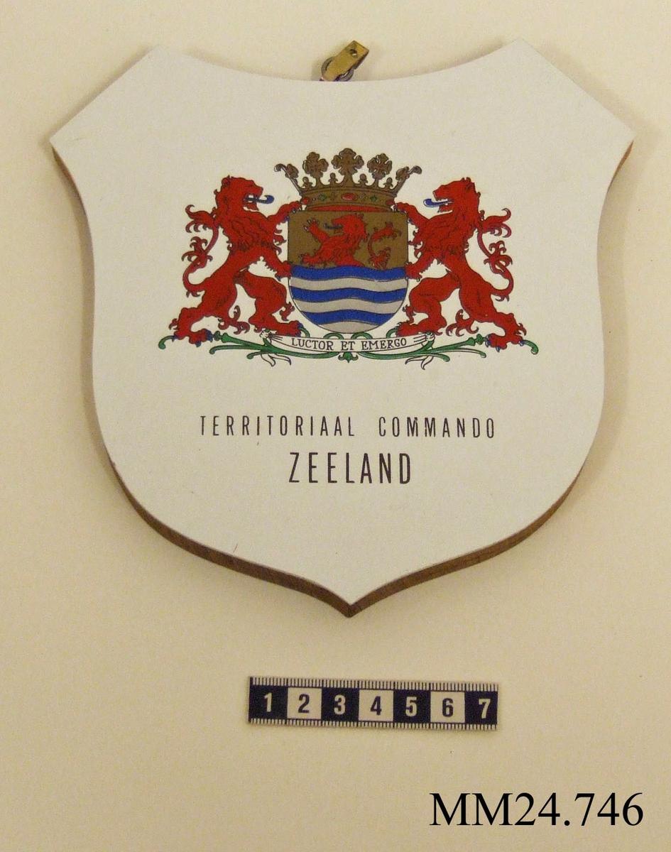 """Träsköld med vit framsida. Målat på den vita ytan är ett heraldiskt vapen bestående av två röda lejon som flankerar en sköld krönt med kungakrona. På skölden syns den holländska provinsen Zeelands vapen bestående av ytterligare ett rött lejon som står på bakbenen med blå och vita vågor upp till midjan.  Under en banderoll med texten """"LUCTOR ET EMERGO"""" (övers. jag kämpar och tar mig fram). Därunder text i guld: """"TERRITORIAL COMMANDO ZEELAND"""".  På baksidan två metallbyglar för upphängning och överst en metallring med krok."""