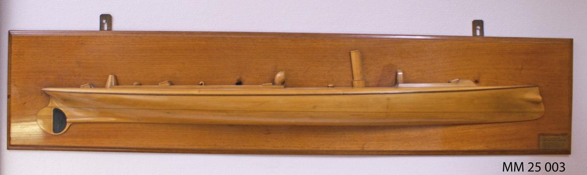 """Halvmodell av fernissat trä föreställande Torpedbåt nr 65. Styrbordssida med däcksdetaljer. Halvmodellen är fäst på fernissad träplatta. I nedre högra hörnet finns mässingsbricka med texten: """"Torpedbåt nr 65, byggd år 1885 vid Kungl flottans varf"""", samt måttuppgifter."""
