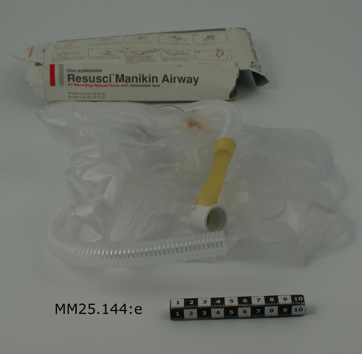 Genomskinliga, räfflade plaströr som förenas i en t-koppling. Ena röret slutar i en gummi-/plastanordning som ska fästas i övningsdockans mun, en del slutar i en gneomskinlig lunga av plast och den sista delen slutar tämligen tvärt. Förvaras i en vit pappkarton med grått och rött tryck som visar hur den ska monteras.