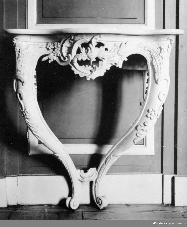 Dekorerat väggfast bord med avsmalnande, inåtgående ben. Gunnebo slott 1930-tal.
