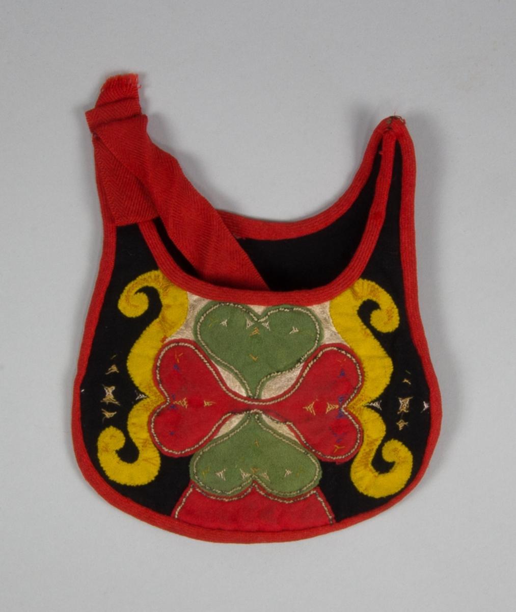 Kjolsäck till dräkt för flicka från Leksands socken, Dalarna. Modell med neråtsvängt framstycke och överkant. Tillverkad av svart ylletyg, kläde, med applikationer av kläde i rött, grönt och gult, samt vitt skinn. Mittfiguren, en hjärtblomma, är fastsydd med läggsöm med metalltråd, nu nästan bortnött. Slingorna på sidan är fästa med kastsöm. Hjärtblomman är monterad ovanpå en bit vitt skinn. Rester av flätsömmar, sydda med silke. Framstycket fodrat med rött bomullstyg, fabriksvävt, kypert. Kantat runtom med rött diagonalvävt ylleband, som kan vara sekundärt. Bakstycke av svart kläde. Axelband fabriksvävt av rött ylle, spetskypert.