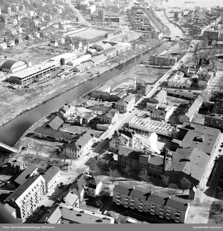 Flygfoto över Storgatan och Selångersån taget från Västra Allén och österut mot Sundsvallsfjärden. Tennishallen, Sundsvalls verkstäder, Idrottsparken och Norrmalm