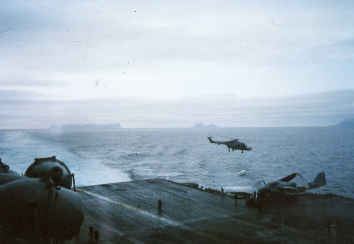 Amerikansk fly av typen A-6 Intruder ombord på Hangarskipet Eisenhower med nr. CVN 69, som er ute i Vestfjorden. I luften sees et norsk helikopter av typen Westland Lynx Mk. 86.