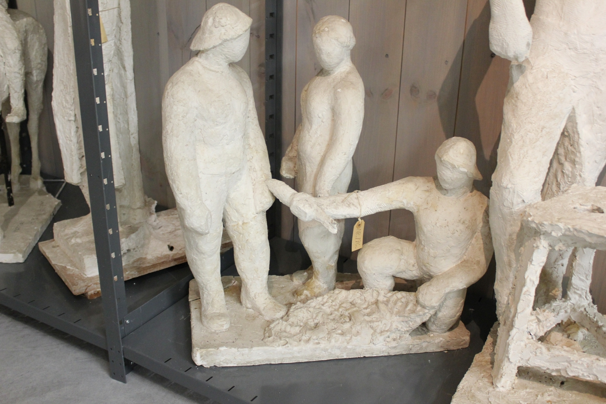 """Skulptur i gips av 1 kvinne og 2 menn som renser garn. Tittel: """"Fiskebrygga"""". Konkurranseutkast. Rådhusplassen i Oslo fra 1936"""