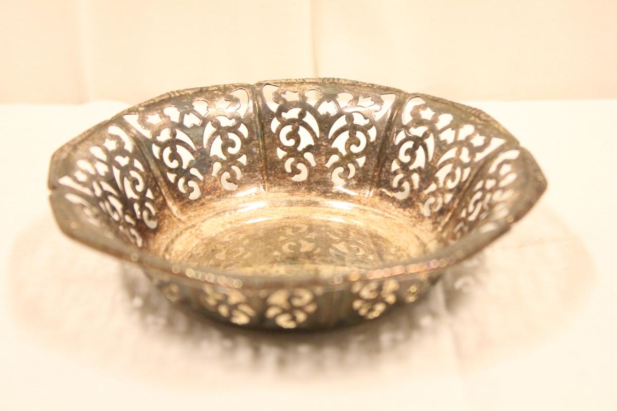 "En lite skål i sølplett med mønstret hullbård rundt hele skålen. Under skålen er det et preget stempel som det står ""Quist"""