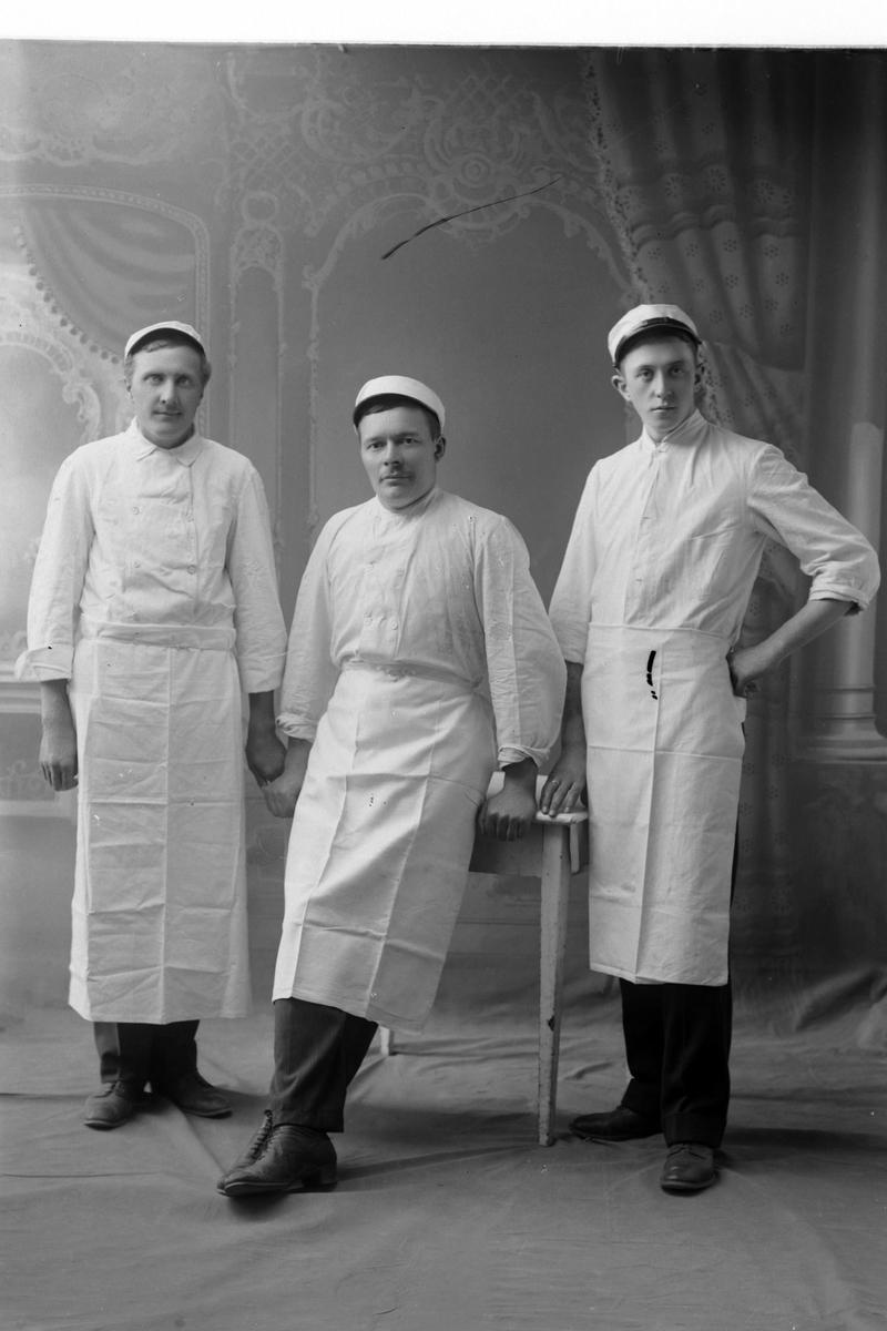 Studioportrett av tre menn i helfigur, iført hvite skjorter, luer og forklær.