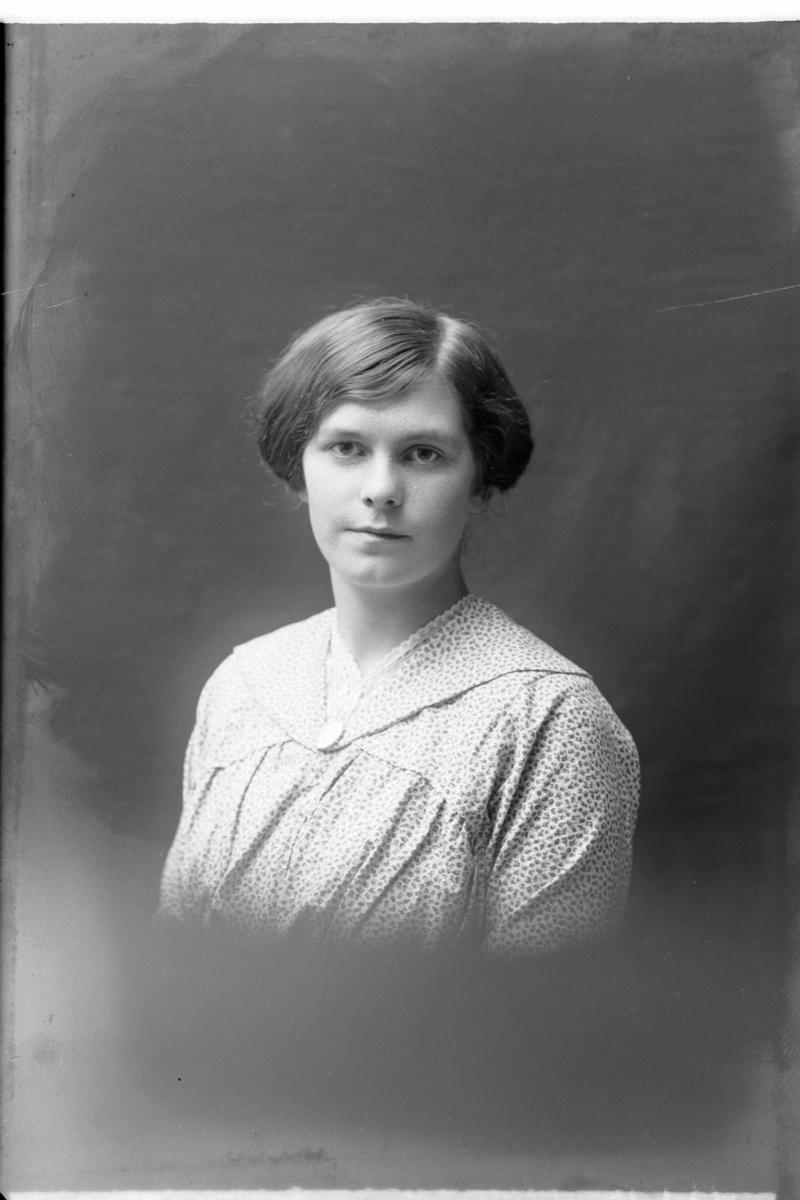Studioportrett av kvinne i halvfigur.
