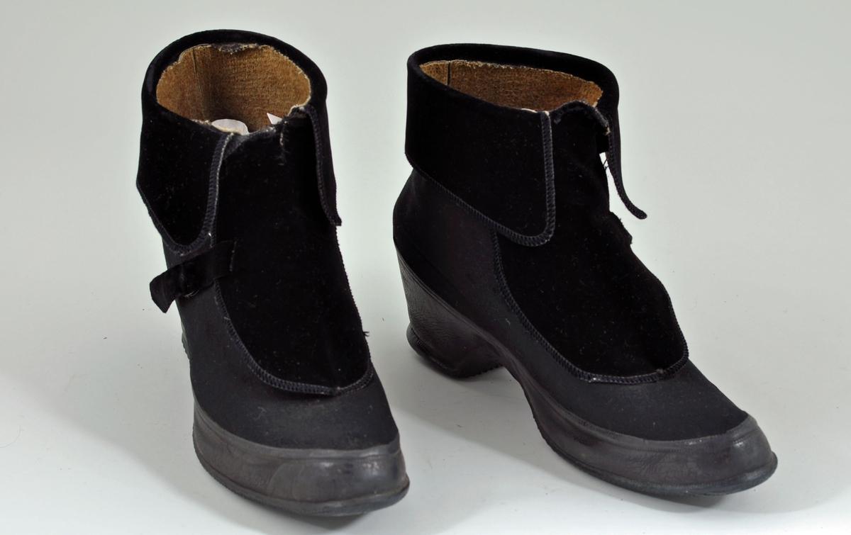 Svarte botforer med gummisåle og overdel av tekstil. Foret. Skoen lukkes over vristen med en sidelengs pløse av fløyel. Nedbrettet pyntekant på skaftet  av fløyet.. Til å ta på utenpå andre sko. Halvhøy hæl.