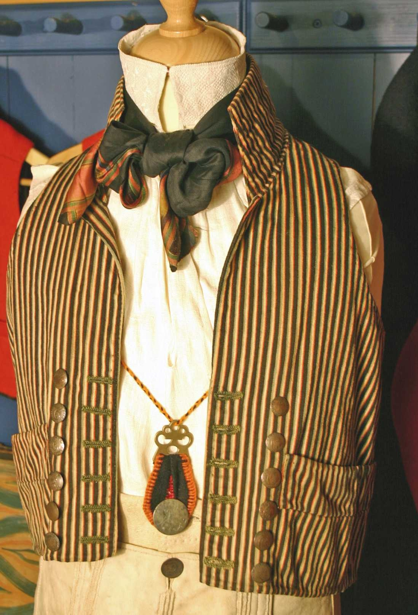 1 vest  Vest av sort og grøn-gul-rød stripet kjøpetøi, foret med strie, rygstykket av hvidt vadmel. Høi krave. Har paa hver side 6 sølvknapper, laget av danske 2 skilling fra aarene 1697, 1761, 1778, 1783, 1784, 1784, 1785, 1786, 1787, 1785, 1802, og 1807. Har været benyttet som brudgomsvest paa gaarden Rebni i Skjolden.  Kjøpt av Lars Skaaren, Skjolden.