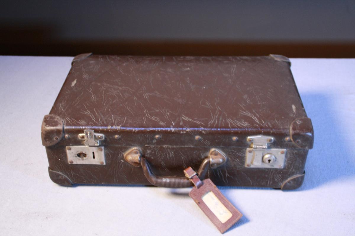 Liten koffert i vulkan fiber. Forsterka hjørner, handtak og to låser. Sett saman med naglar. Trekt med stripete papir inni. Fleire blekkflekkar. Adresselapp.
