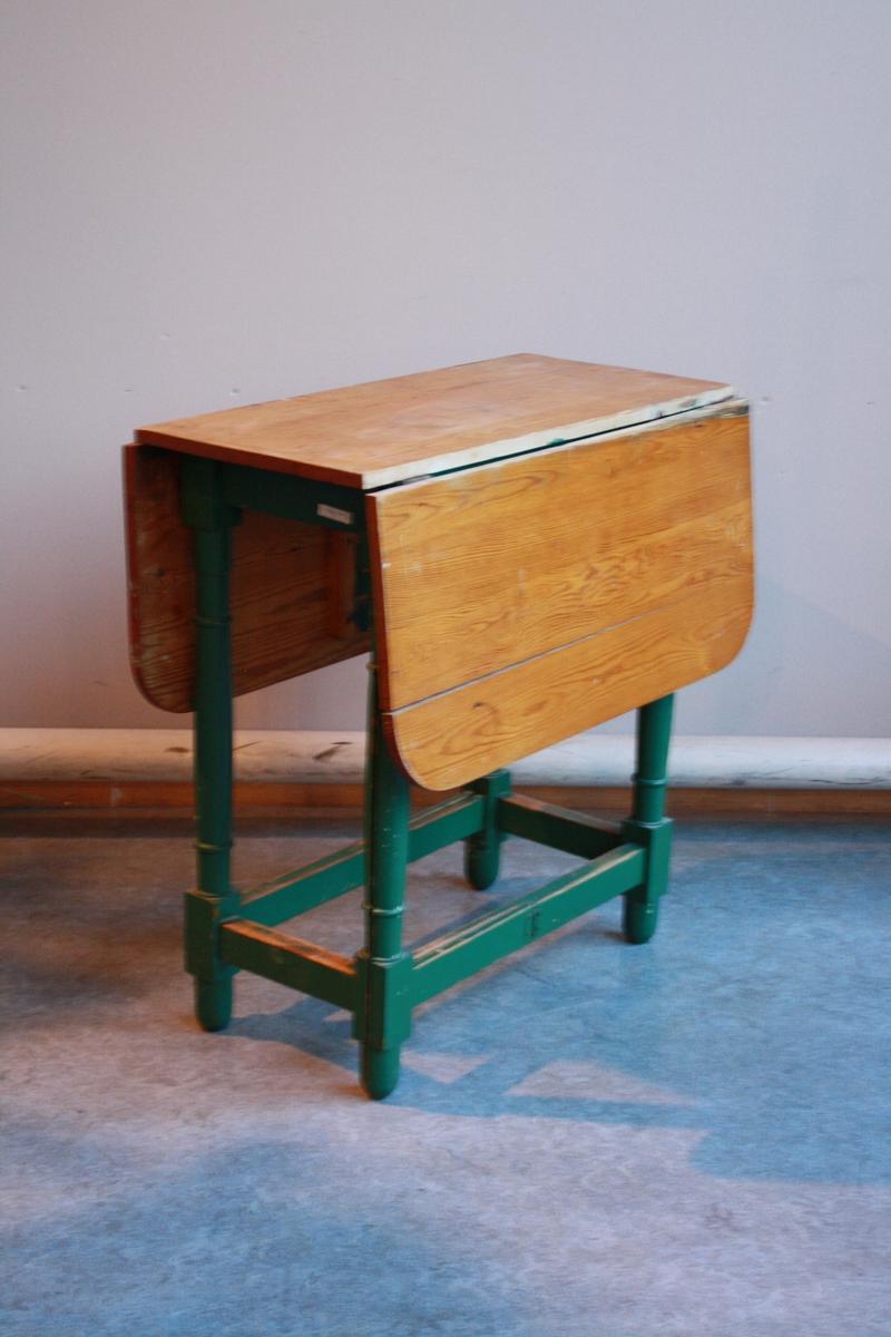 Bord med to klaffer. Fire bein, to delte langsgåande slik at dei kan slåast ut og støtte kvar sin klaff. Understell grønmalt, bordplate lakkert furu.