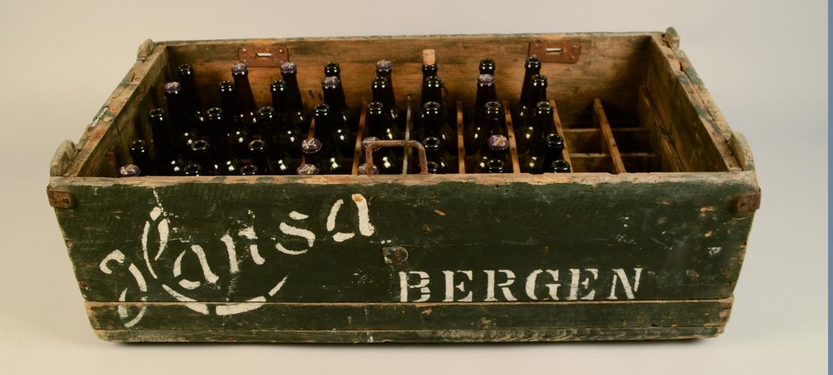 """Ei trekasse med lok. Oppdelt i femti rom inni, med plass til femti ølflasker, ei i kvart rom. Jarnbeslag og lukkemekanisme. Flasker merka """"bok øl"""" fylgjer med, alle tomme, men nokre har kapsel på. Det fylgjer også med ein lapp frå Hansa Bryggeri til P.K.Mardal Sandane. Det er også lapp stifta på kassa. Flasker: etikett på blå botn med tekst. Mørk grønt glas. Mørk blå kork."""