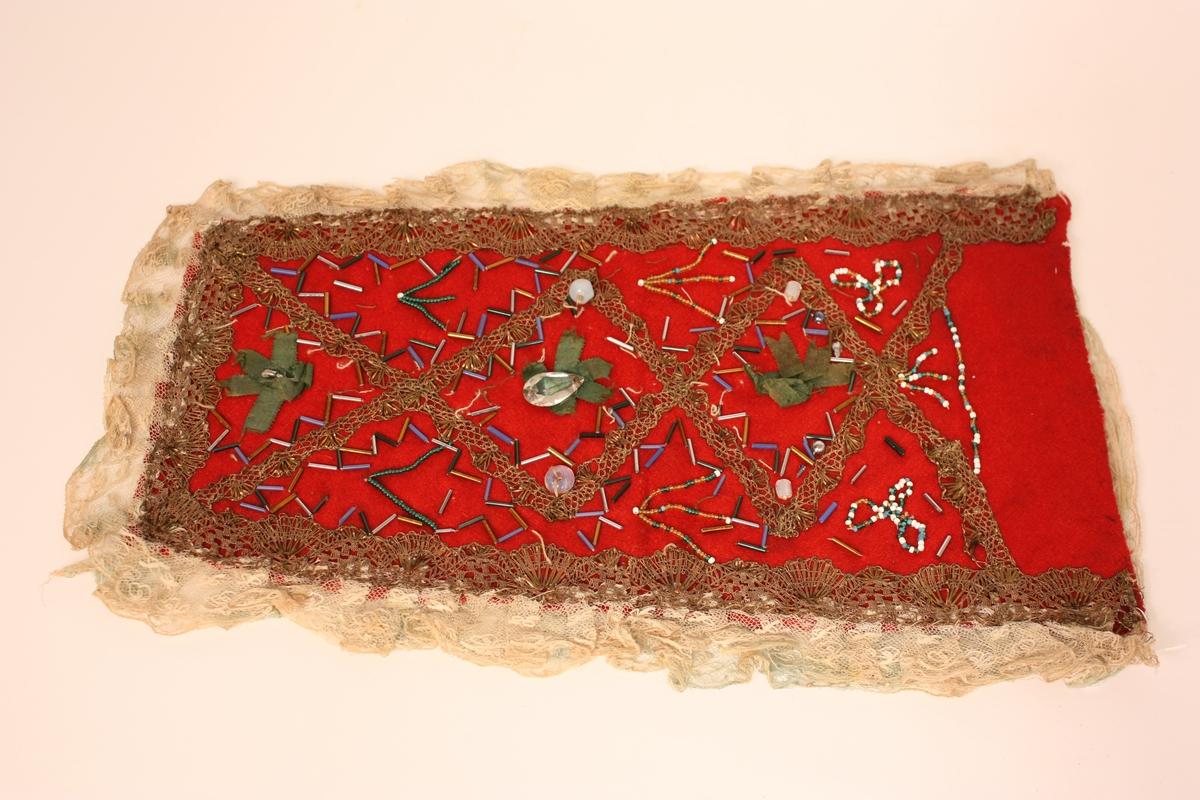 Sikksakkmotiv langs kanten i rutene. Silkerosettar med perle i midten. Blome- og stråliknande motiv i dei andre rutene.