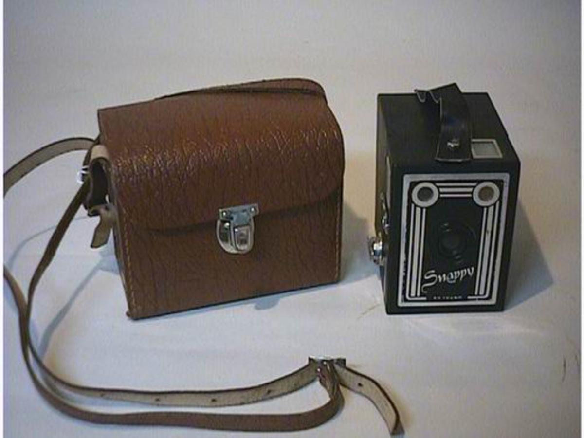 Kasseapparat med all mekanisme innebygd. Tilhøyrande kameraveske i skai.