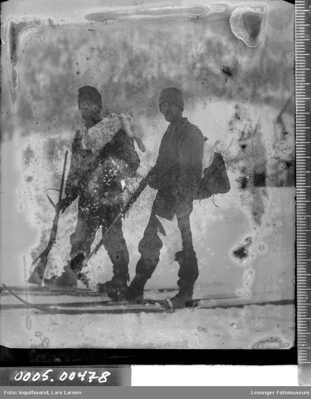 Portrett av to på ski som er på jakt, med geværer, skutt hare og rype.