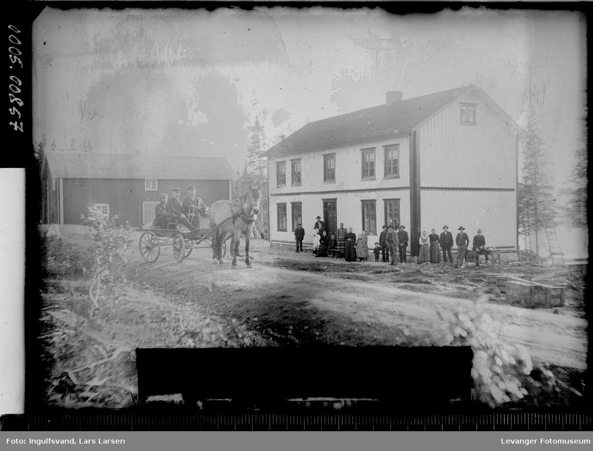 En gruppe mennesker og hest og vogn foran en bygning.