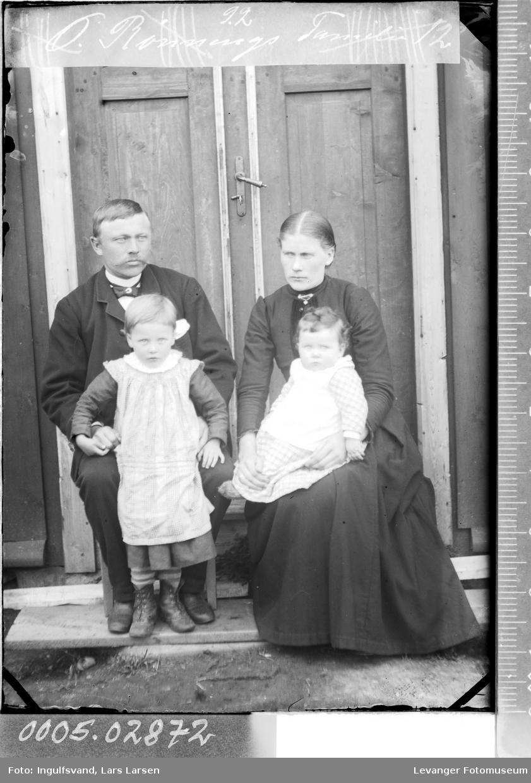 Gruppebilde av kvinne, mann og to barn ved et inngangsparti.