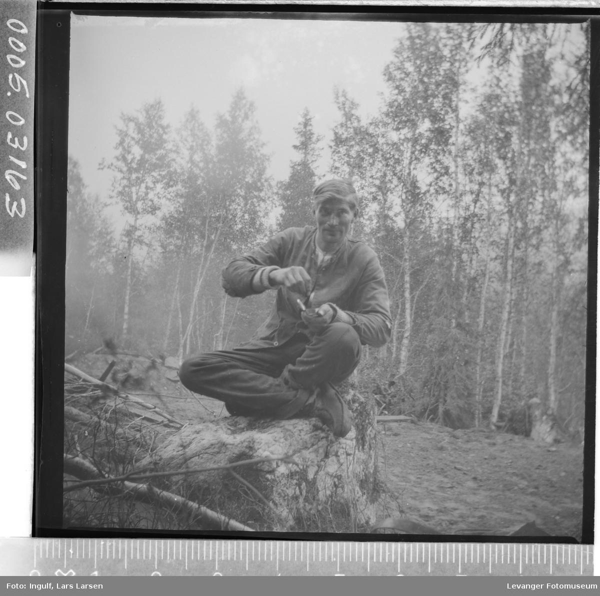 Portrett av mann som sitter på en trerot.