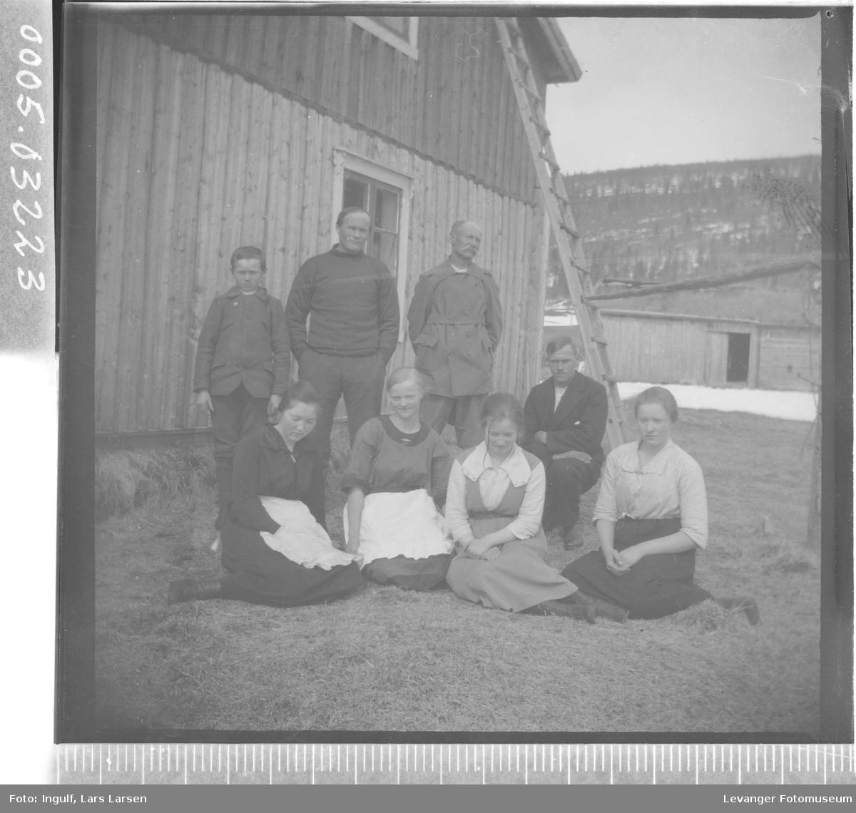 Gruppebilde av fire kvinner, tre menn og en gutt ved en bygning.