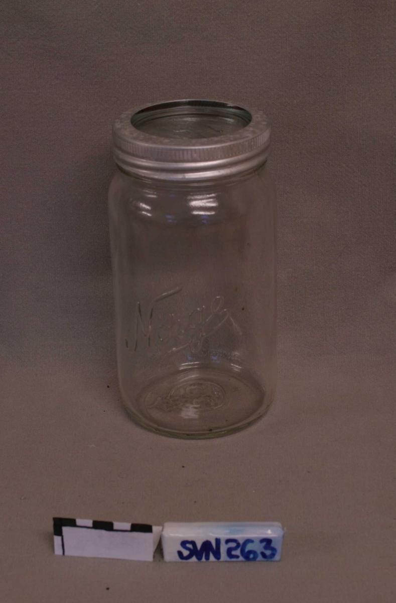 Del A: Krukke i glass med rund base, og skruriller ved åpningen. Del B: Skiv i glass med svakt fortykket kant. Del C: Festering til lokk, i metall, med skruriller på innsiden. Del D: Isoleringsring til å legge på krukkens kant. Ringen er i rødt gummimateriale.