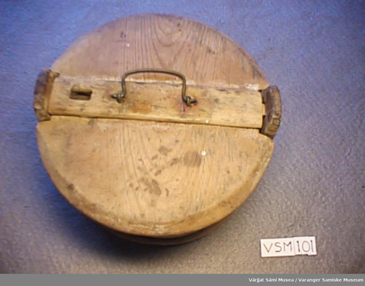 Rund smørdall av tre. Den har 2 ører med hull i. Når lokket legges på låses det på den måten at lokket har et lite spor som treffer en av hullene på det ene øret. På lokket er det et lite jernhåndtak. Rundt dallen (på utsida) er det tvunnet en ring av tre. Under dallen er det rispet inn: 1189.