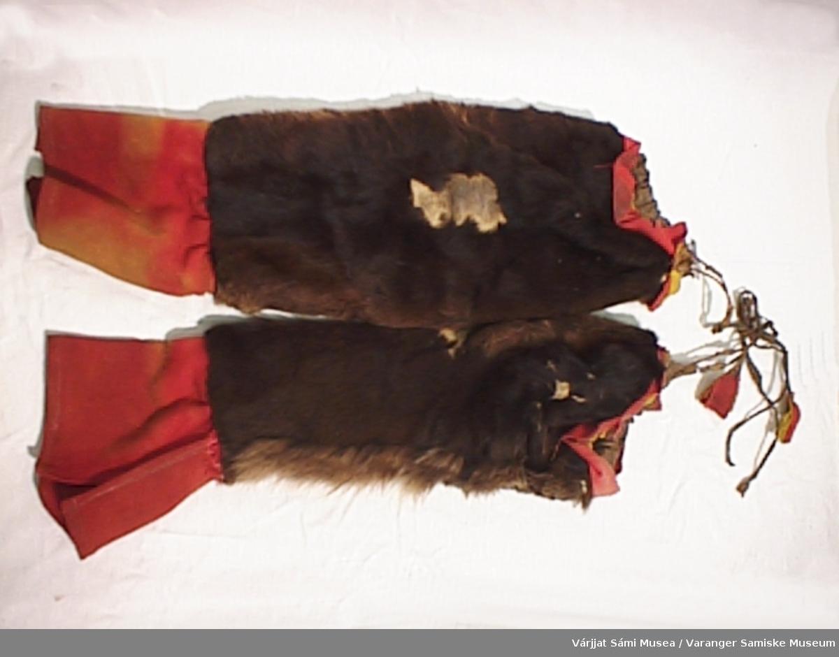 Et par herrebellinger sydd av mykt mørkebrunt skinn med pelsen på, pyntet øverst med rødt og gult klede samt en skinnanor med klededusk til stramming, rødt stykke av en annen type tøy nederst.