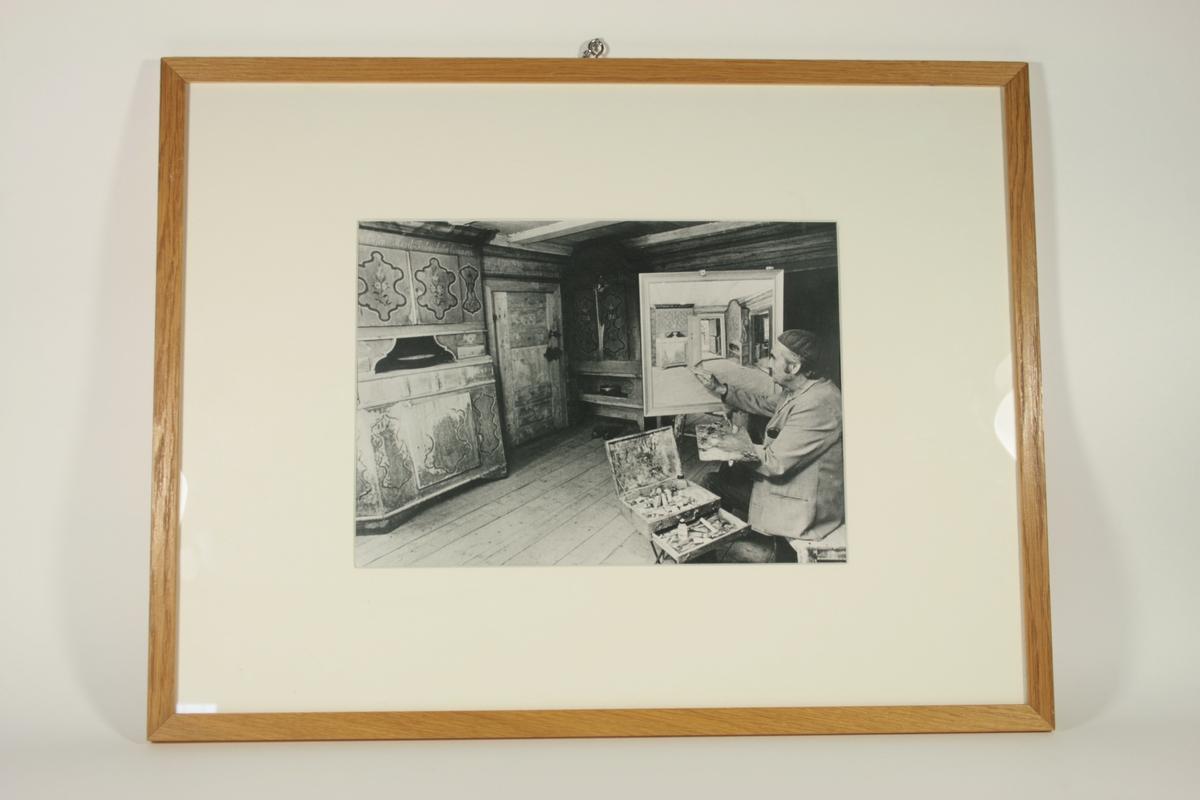 Fotografiet viser en mann som maler et interiørbilde. Han sitter til høyre i bildet med maleriet vendt mot fotografen. Maleriet er innrammet og  viser interiøret i rommet han sitter i, med et rosemalt treskap helt til venstre i bildet, så en dør og videre til høyre, et nytt rosemalt treskap, og så en ny dør. Ved siden av mannen er et åpent treskrin med malingstuber som står på et stativ. Maleren selv er kledt i en mørk alpelue, rutete blazer og mørke bukser. Han holder et palett med maling på i venstre hånd, og en pensel mot maleriet i høyre hånd.   Motivet kan være iscenesatt da maleriet allerede virker ferdig, samt at det er innrammet.
