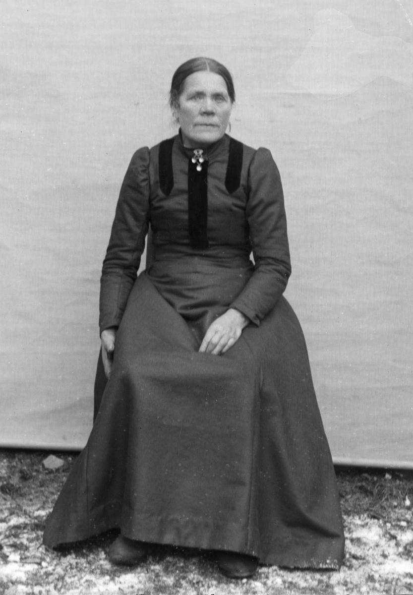 Sittende kvinne kledd i mørk kjole, foran hvitt lerret