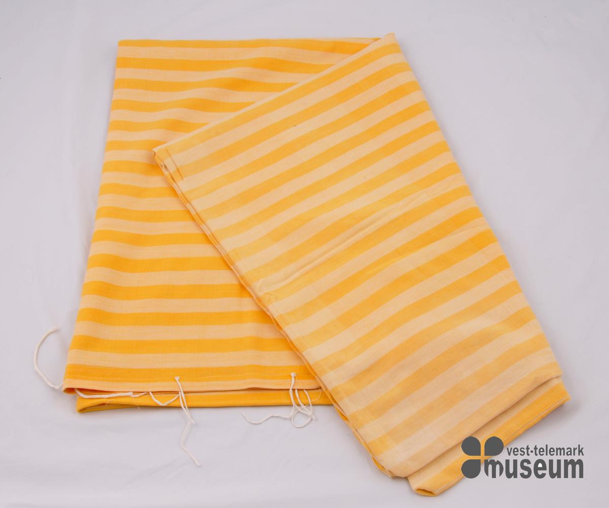 Heimevove dynetrekk i langsgåande striper. Sydd saman av to lengder. Opning på sida med kvite bandelband, 5 sett.