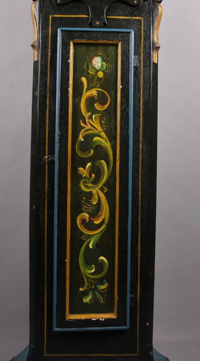 Golvklokke, mørk grønmåla med rosemåla parti i gult, grønt, raudt og kvitt. Fire marmorera søyler på toppen av kassa.  Urverket  og skiva er i messing og jern. Det er to lodd, ein pendel, ein nykel og ei skive der loddtråden rullar etter som høyrer til urverket.