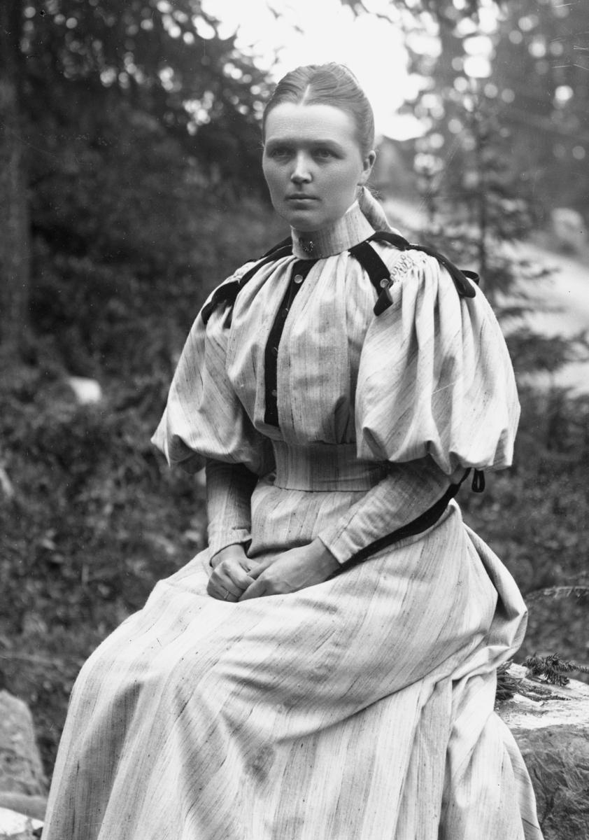 Kvinne sittende på stein, med skog i bakgrunnen