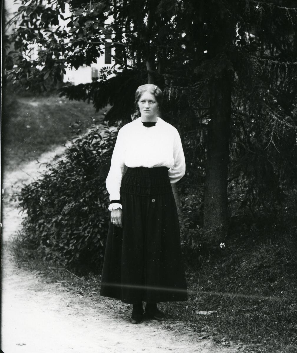 Kvinne i helfigur, kledd i hvit skjorte og mørkt skjørt, fotografert på vei med skog og hvit bygning i bakgrunnen
