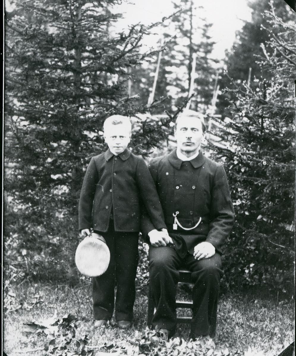 Mann og gutt, skog og skigard i bakgrunnen