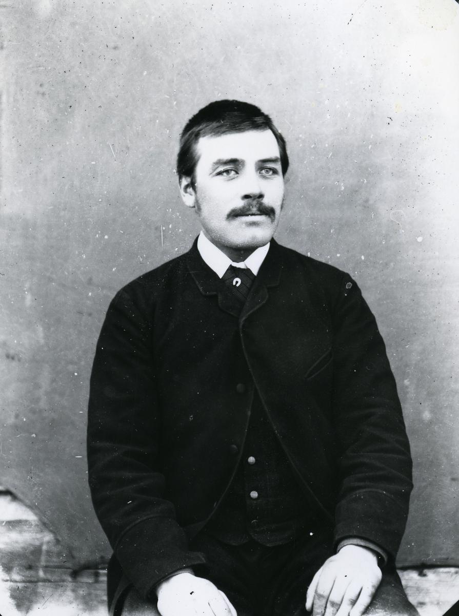 Mann sittende foran lerret