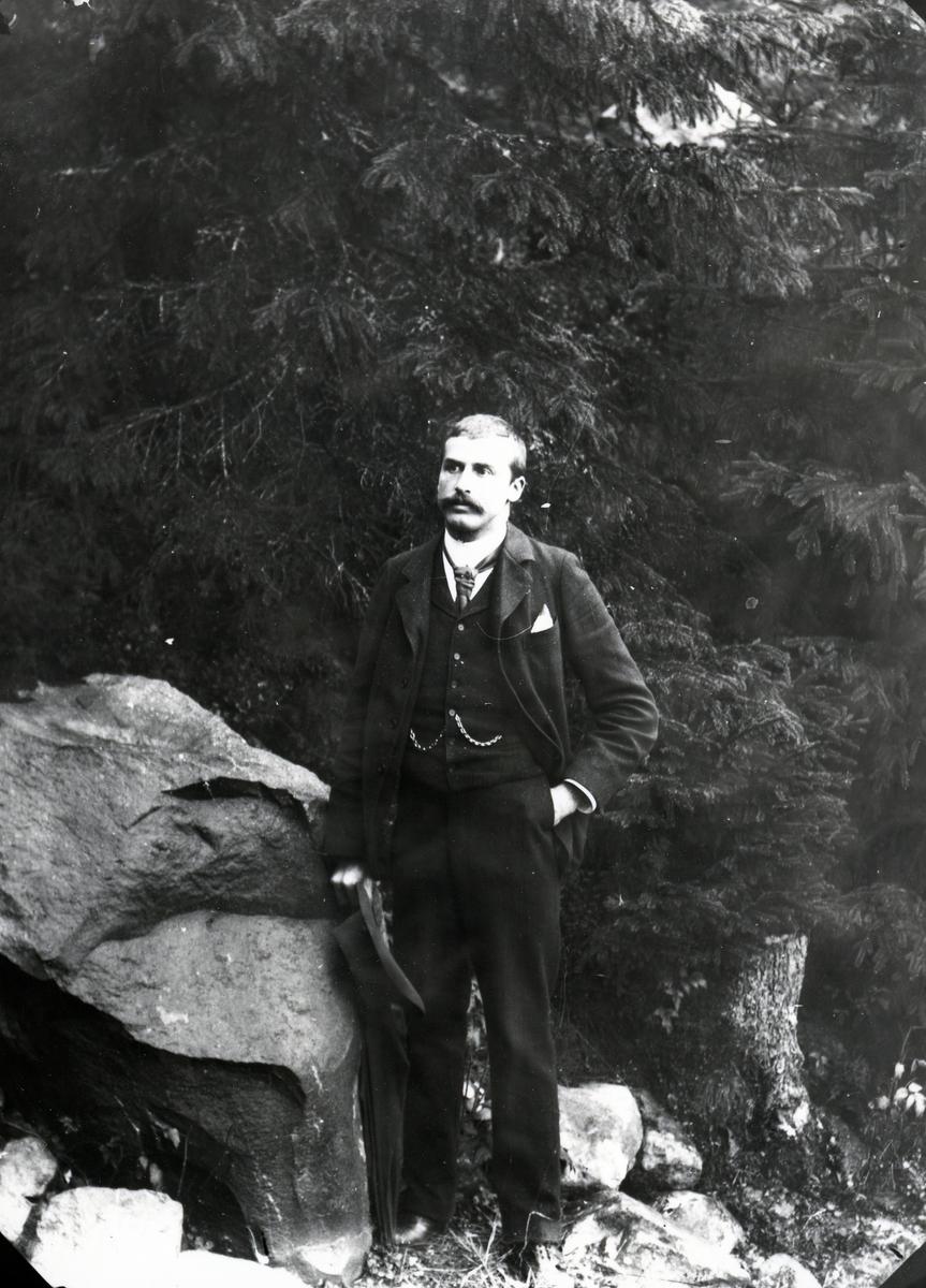 Dresskledd mann med hatt i hånda, stående ved stein, foran skog