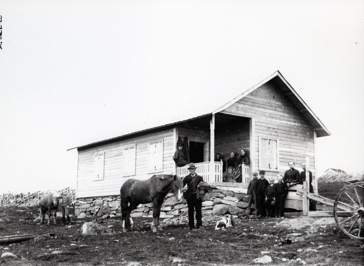 Mennesker samlet utenfor hus, antagelig stølssæl, sammen med hund og to hester