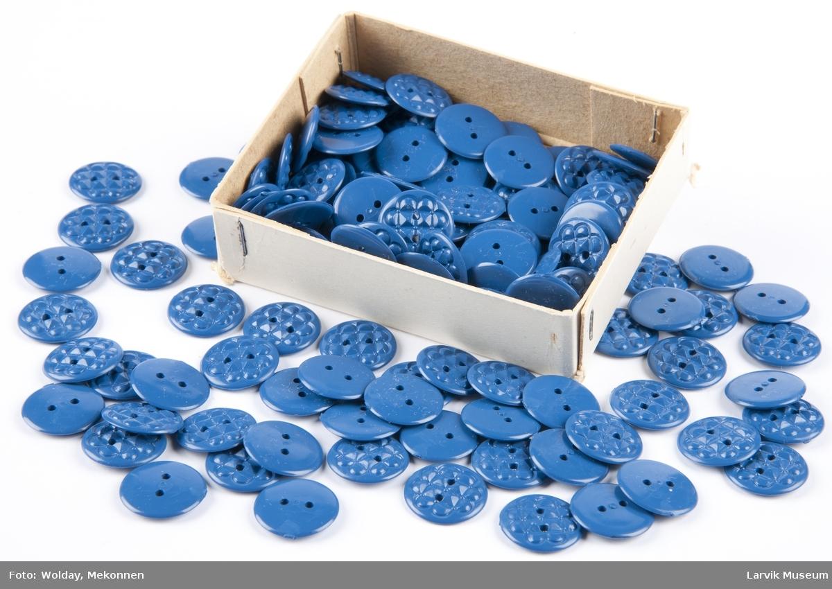 Uttallige knapper i en pappeske m/lokk. En knapp montert på utsiden av lokket