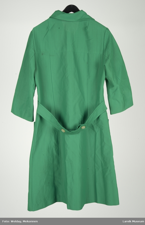 Arbeidsforkle/kjole, innsvinget, 7 knappehull, 6 tinnknapper, 2 lommer foran pluss en brystlomme, belte bak med 2 knapper, 3/4 lange ermer