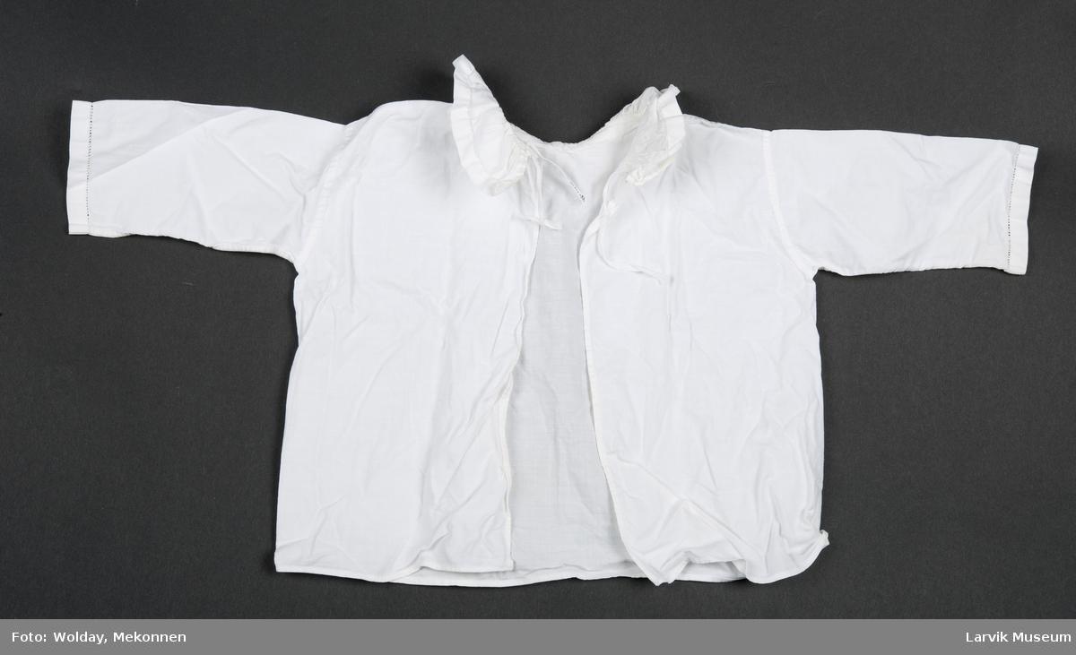 Langermet, kort bluse med rund krave. Hullsøm på krave og ermer.