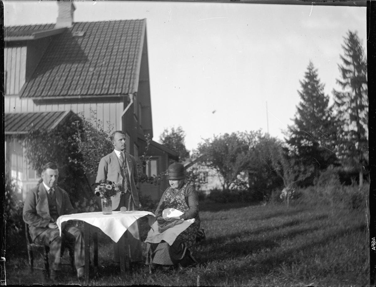 Vid ett bord i trädgården. Troligen i aug, 1931. Mamma, Anders och jag.