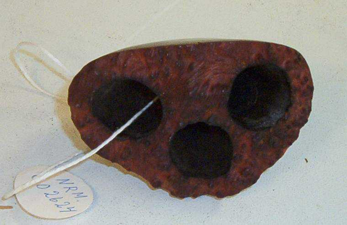 Hasjpipe av laget av tre. Tre hull på toppen av en traktformet trebit. Pipeskaftet mangler.