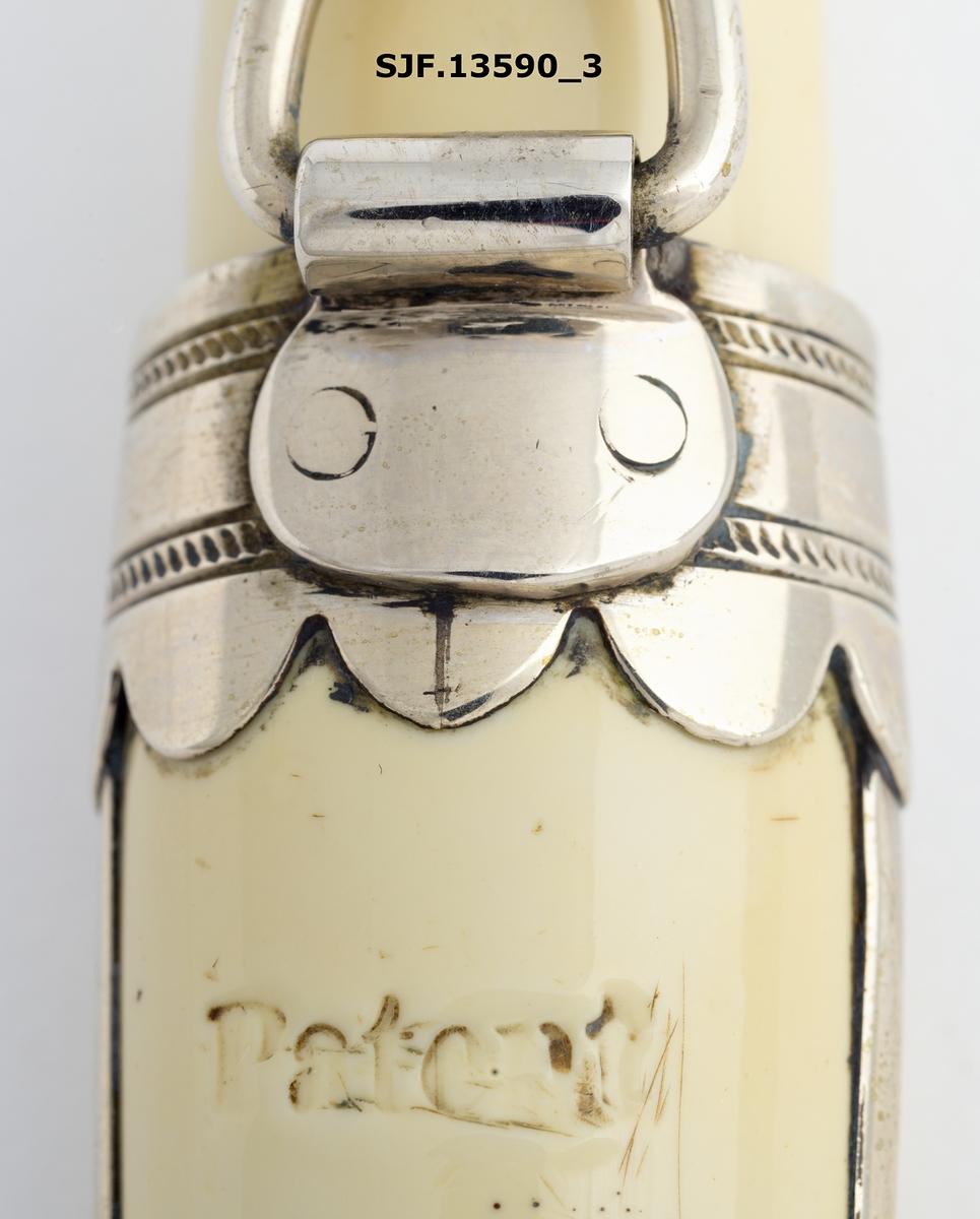 Kniv med slire laget av knivmakeren Petter Knutson Flølo (1847/1848-1927) fra Nordfjord, Gloppen kommune (Sandane),  i Sogn og Fjordane. Skaft og slire er laget av metall som er kledd med hvit hardgummi. Holkene er av nysølv.