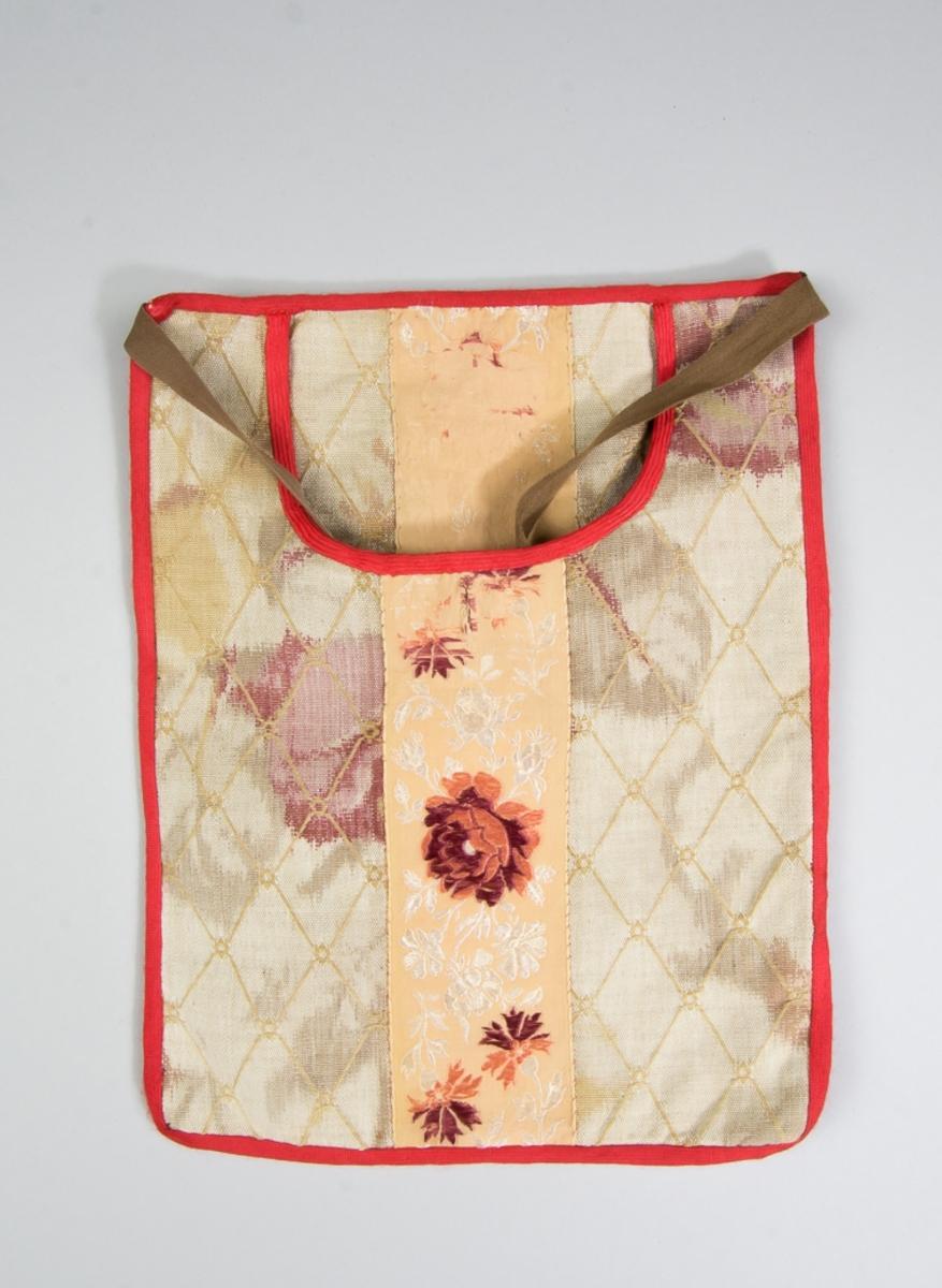 Kjolsäck till dräkt för kvinna från Västra Vingåkers socken, Södermanland. Modell med u-formad öppning. Tillverkad av  mönstervävt fabrikstillverkat bomullstyg, beige med vävt rutmönster samt tryck i bruna och rosa toner. I mitten lodrätt ett mönstervävt band av siden, med jacuardvävd blomsterslinga i rött och vitt på beige botten. Strax under öppningen ett knapphål, sytt med brun tråd. Knappen är av syntet, brun. Öppningen kantad runtom med diagonalvävt rött konstsilkeband, samma band runtom. Framstycket är fodrat med linnetyg, samma som bakstycket. Bakstycke tillverkat av fabriksvävt linnetyg i tuskaft. Midjeband bruna, av bomull.