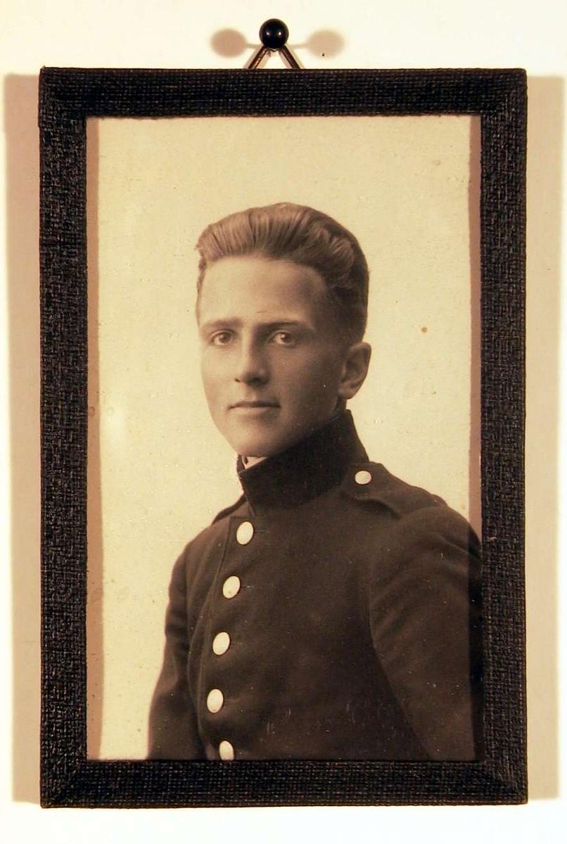 Portrett av ung mann i uniform. Han ser direkte på betrakteren.