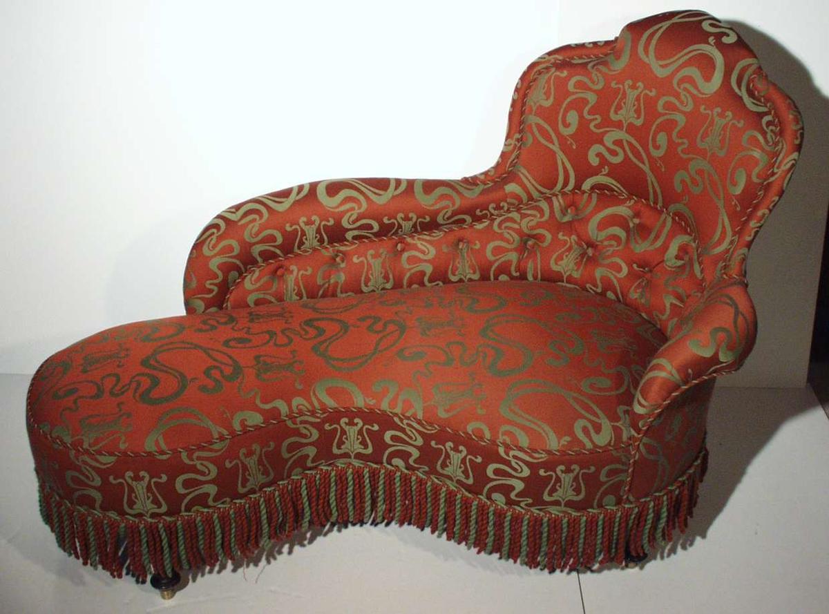 Sengelignende sofa med et svunget og tre dreide ben. Et kort og et langt armlene.