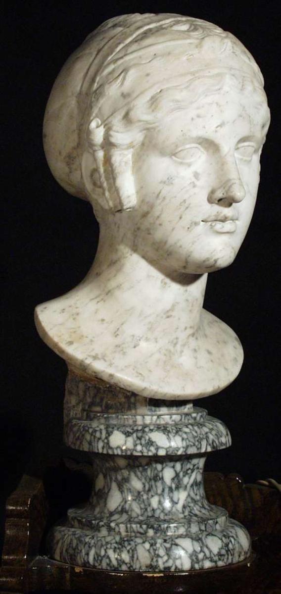 Kvinnehode i marmor med rund sokkel.
