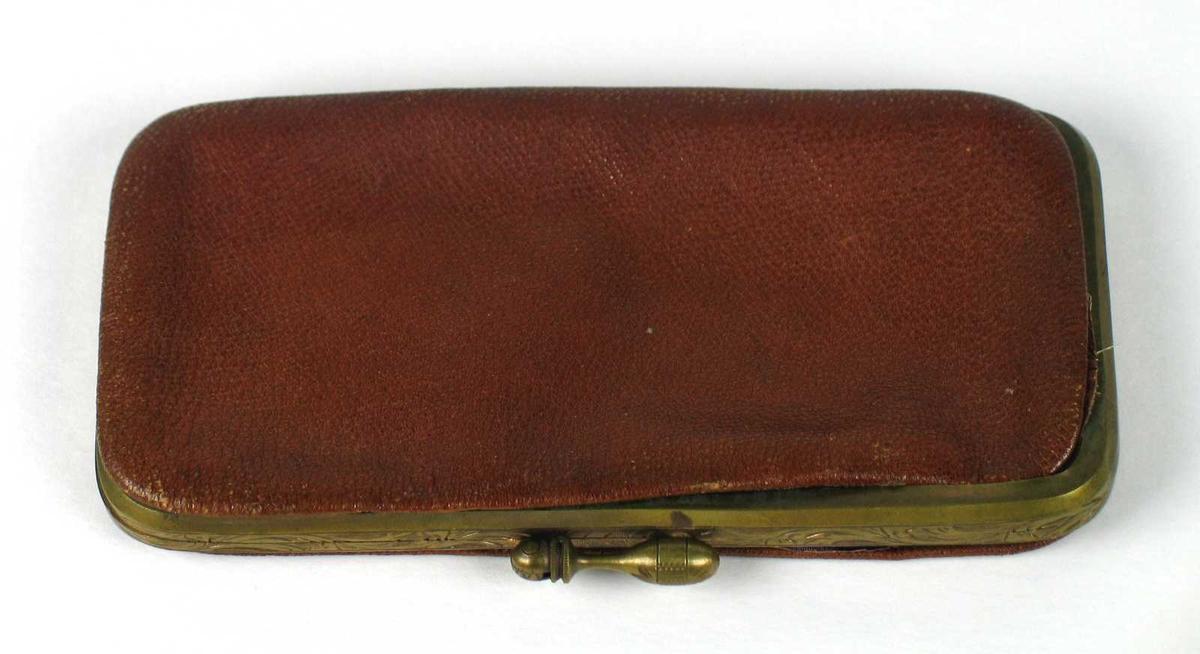 Brilleetui i brunt skinn fôret med lilla silke. Etuiet har messingkanter med gravert bord og lås.