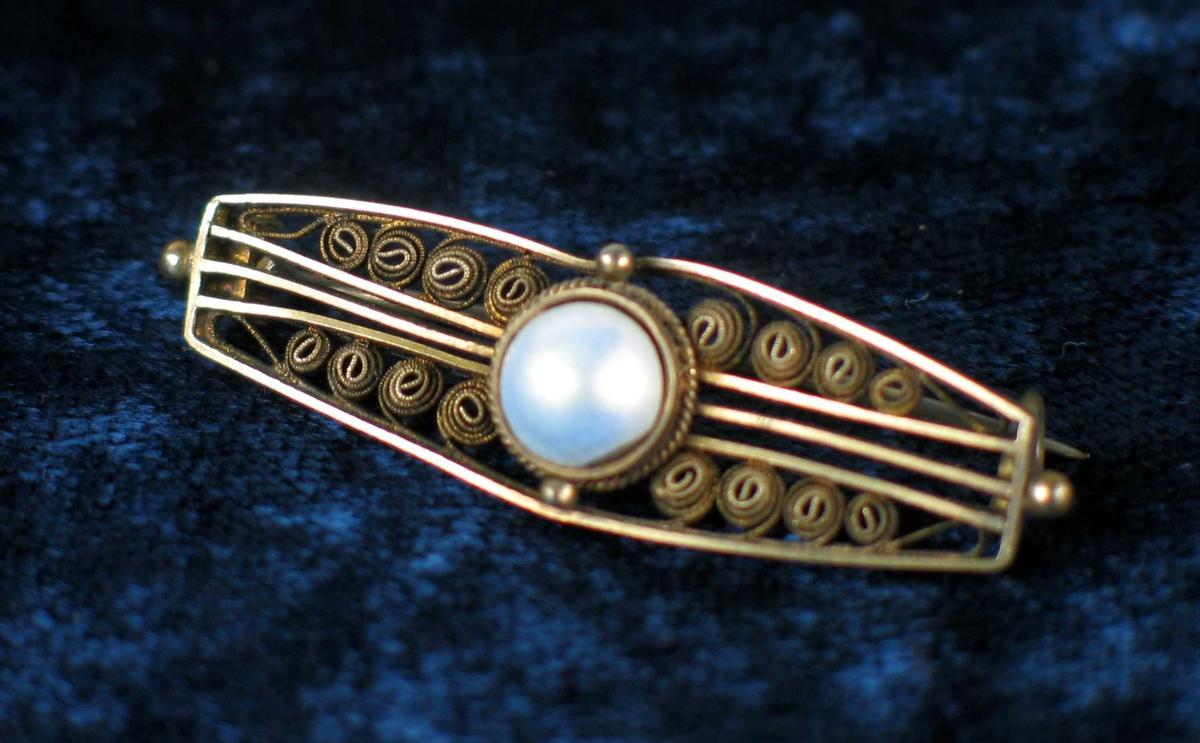 Nål i sølv med perle og filigransdekor.